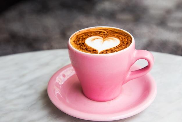 Copo do cappuccino com arte do latte do coração no fundo de mármore da tabela. Foto Premium