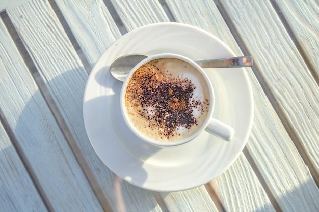 Copo do cappuccino com arte do latte na tabela branca de madeira. vista do topo. Foto Premium