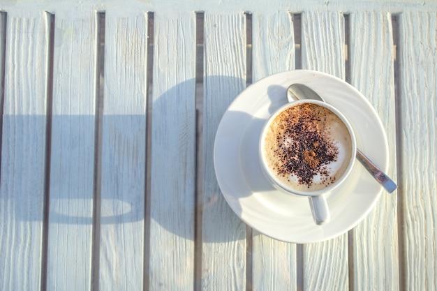 Copo do cappuccino com arte do latte no fundo branco de madeira. vista do topo. Foto Premium