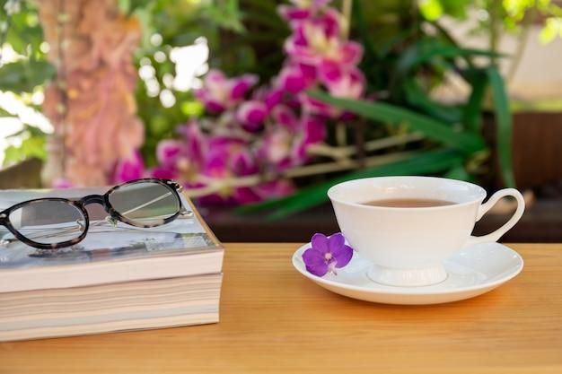 Copo do chá com livros e vidros dos olhos na tabela de madeira no jardim. Foto Premium