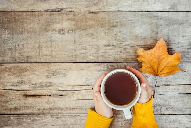 Copo do chá nas mãos de uma criança e de um fundo acolhedor do outono. foco seletivo. Foto Premium