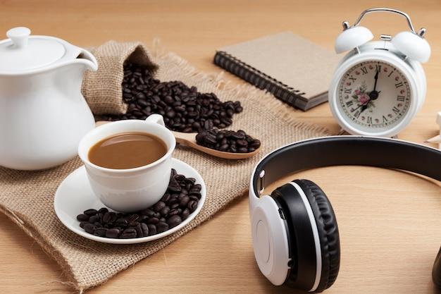 Copo e auscultadores de café no fundo de madeira da prancha. Foto Premium
