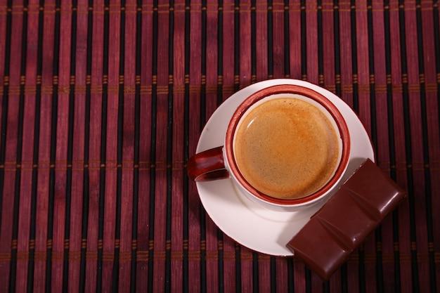 Copo e chocolate de café na textura de madeira da tabela. Foto Premium