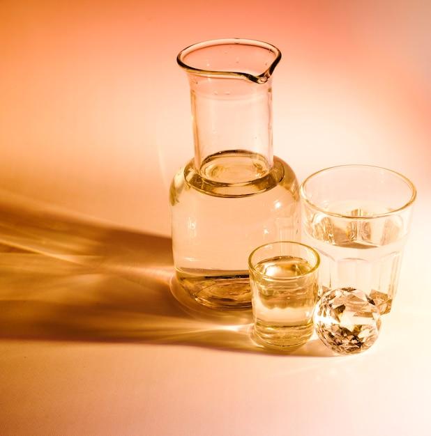 Copo e dois copos de água com sombra no fundo colorido Foto gratuita