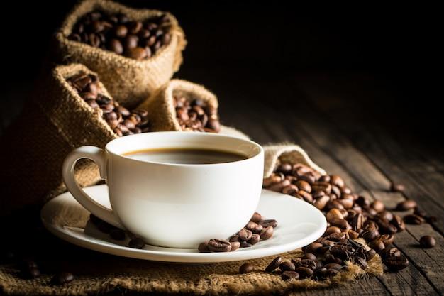 Copo e feijões de café em um fundo rústico. Foto Premium