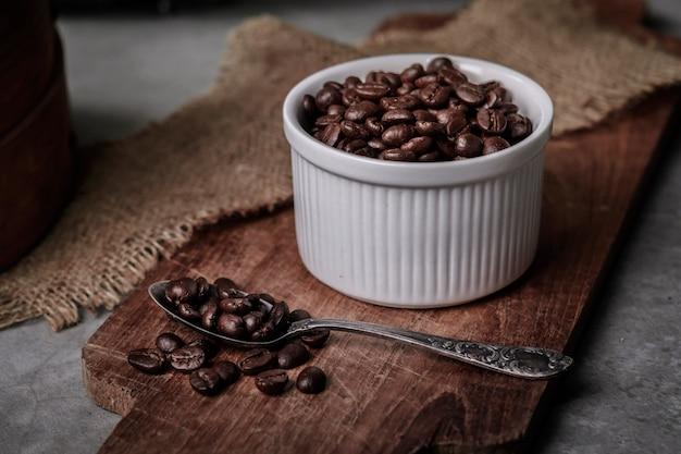 Copo e feijões de café na mesa de cozinha velha. Foto Premium