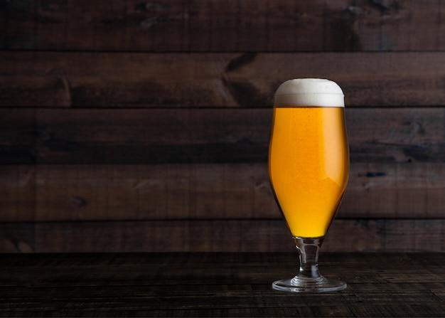 Copo e garrafa de cerveja dourada com espuma no fundo da mesa de madeira Foto Premium