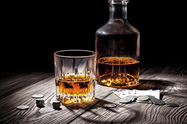 Copo e garrafa de uísque e baralho e dinheiro Foto Premium