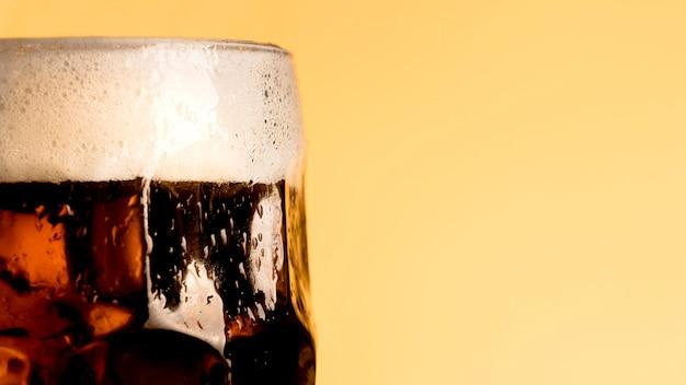 Copo fresco de cerveja em fundo laranja Foto gratuita