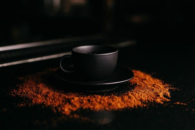 Copo preto de vista frontal no chão de chocolate em pó Foto gratuita