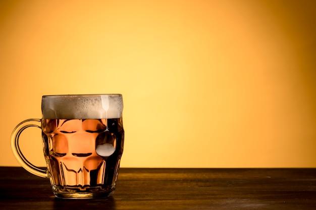 Copo transparente de mesa de madeira de cerveja Foto gratuita
