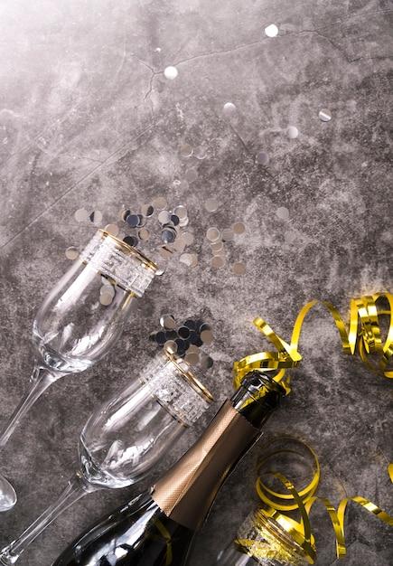 Copo vazio e garrafa de champanhe com item decorativo de festa no plano de fundo texturizado concreto Foto gratuita