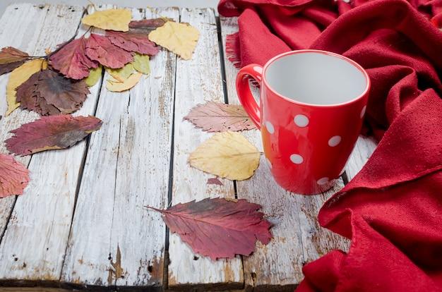 Copo vazio para o chá, folhas vermelhas secas no dia do outono Foto Premium