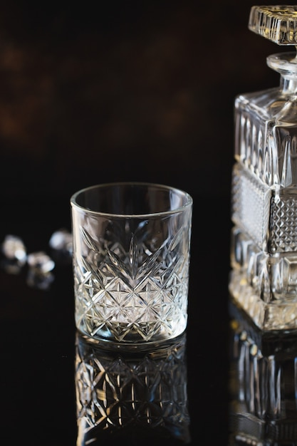Copo vazio para uísque ou bourbon com uma garrafa quadrada de cristal Foto Premium