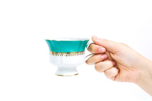 Copo verde do chá à disposição no fundo branco. mão segurando xícara Foto Premium