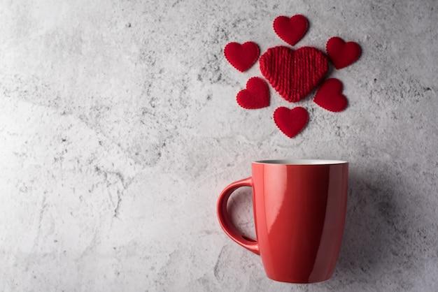 Copo vermelho com coração, conceito de dia dos namorados Foto gratuita