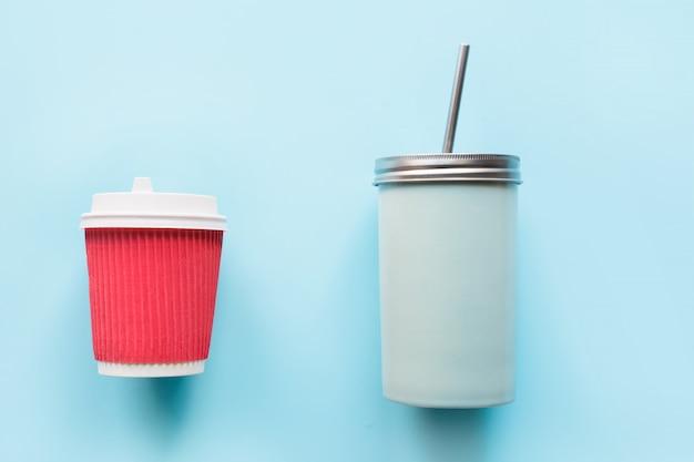Copo vermelho de papel descartável e caneca reutilizável no azul. Foto Premium