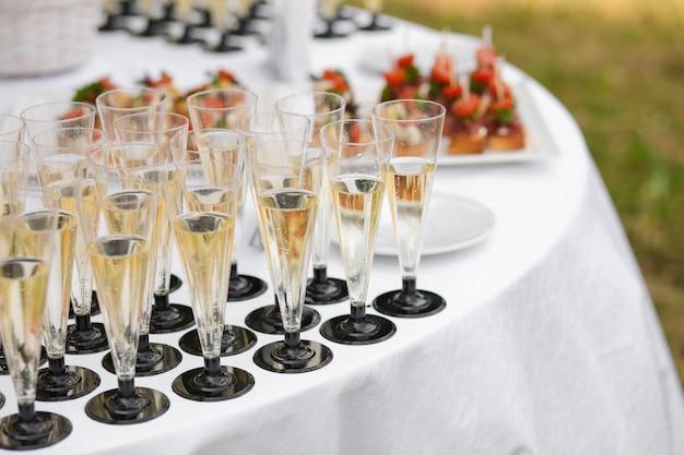 Copos com champanhe, servidos na mesa perto de aperitivos Foto Premium