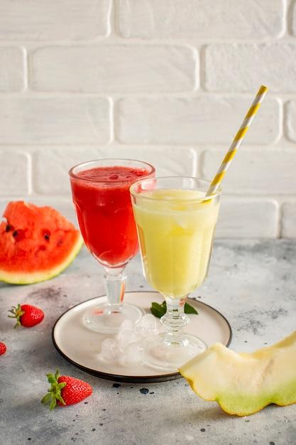 Copos com suco de melancia vermelho e amarelo Foto gratuita