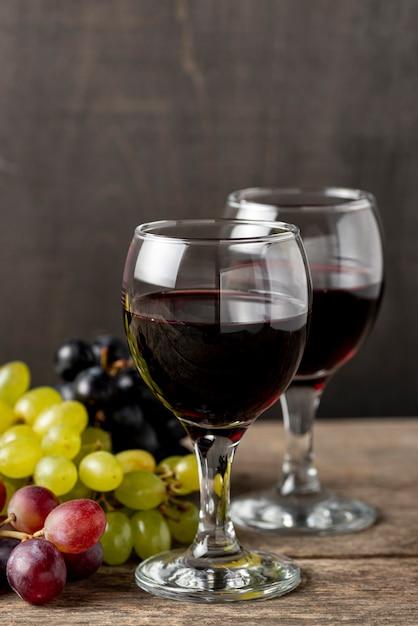 Copos com vinho tinto ao lado de uvas orgânicas Foto gratuita
