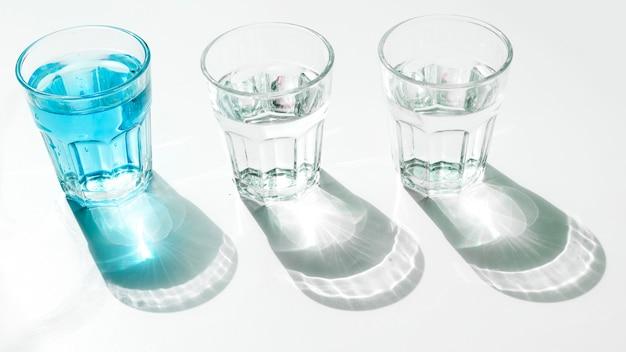 Copos de água azul com sombra no pano de fundo branco Foto gratuita