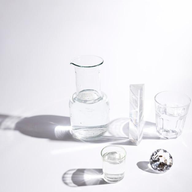Copos de água; prisma; diamante cintilante e copo com sombra no fundo branco Foto gratuita