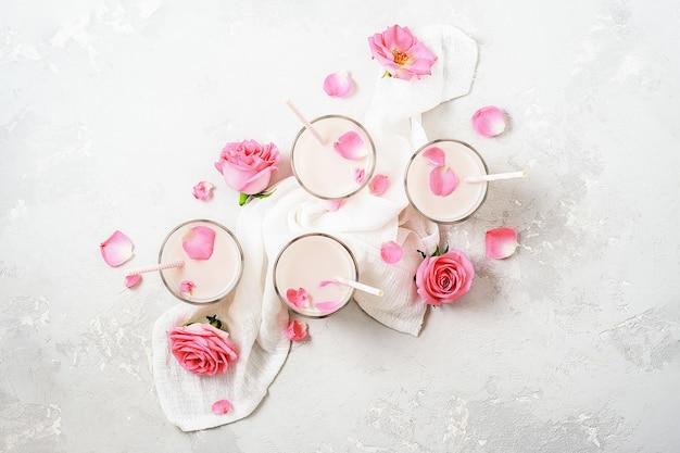 Copos de bebida de leite de lua com rosas em um fundo de concreto. vista do topo. Foto Premium