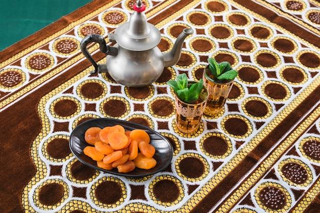 Copos de bebida perto de bule e damascos secos na esteira Foto gratuita