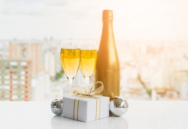 Copos de bebida perto de caixa de presente e garrafa Foto gratuita