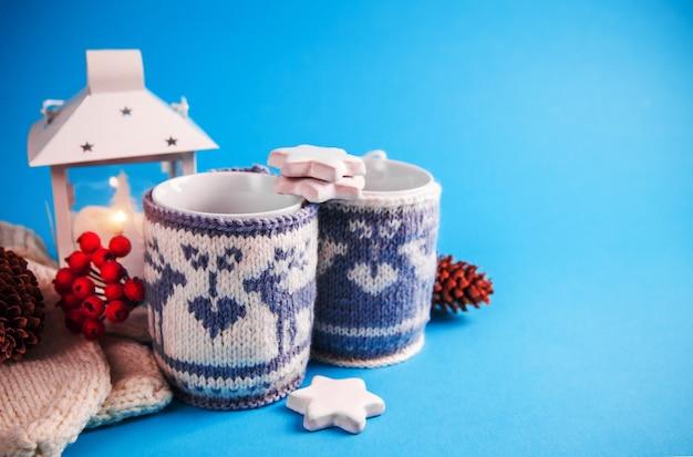 Copos de bebida quente vestidos em casos de natal de malha sobre fundo azul. Foto Premium