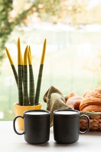 Copos de café com croissants de vista frontal Foto gratuita