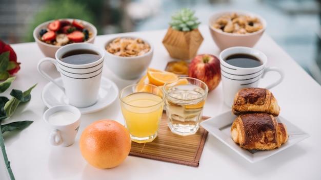 Copos de café com pães doces e suco na mesa Foto gratuita