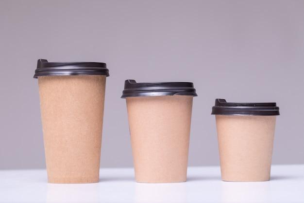 Copos de café de papel coberto tamanhos diferentes isolados em cinza Foto gratuita