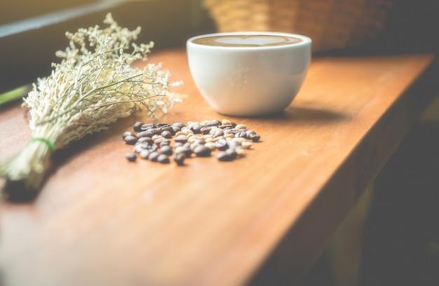 Copos de café, feijões de café e flores secadas em uma tabela de madeira. esta imagem é foco borrado e macio. Foto Premium