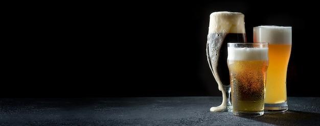 Copos de cerveja clara, escura e trigo em um fundo escuro Foto Premium
