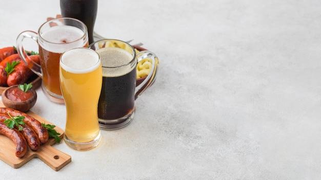 Copos de cerveja de ângulo alto e salsichas Foto Premium