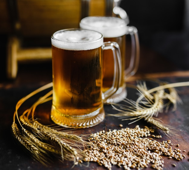 Copos de cerveja e especiarias de trigo em uma velha mesa de madeira rústica em fundo preto Foto Premium