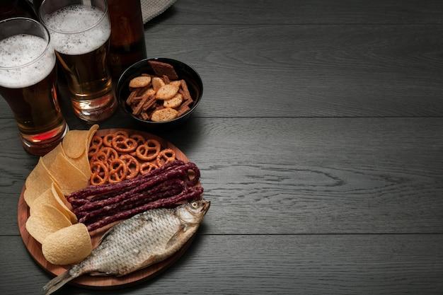 Copos de cerveja e prato de comida com espaço de cópia Foto gratuita