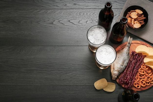 Copos de cerveja plana leigos e prato de comida com espaço de cópia Foto gratuita