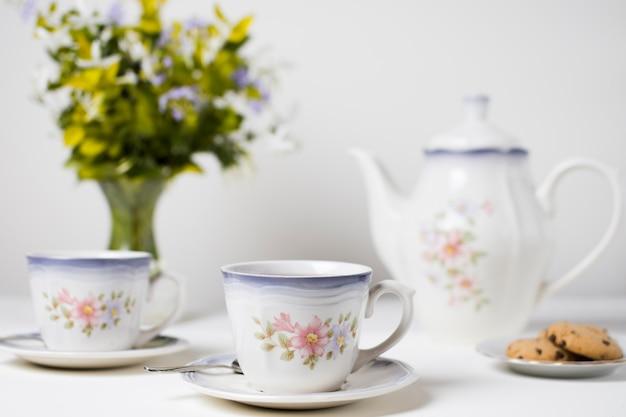 Copos de chá de cerâmica e cookies na mesa branca Foto gratuita