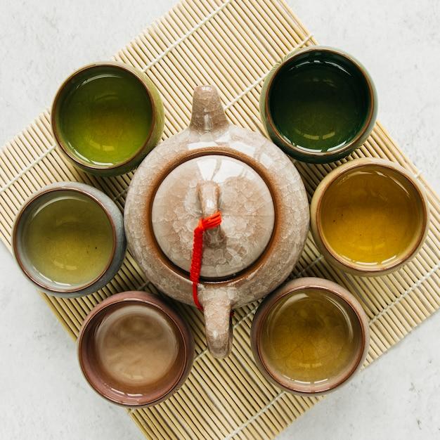 Copos de chá de cerâmica rodeados com bule no placemat sobre o pano de fundo concreto Foto gratuita