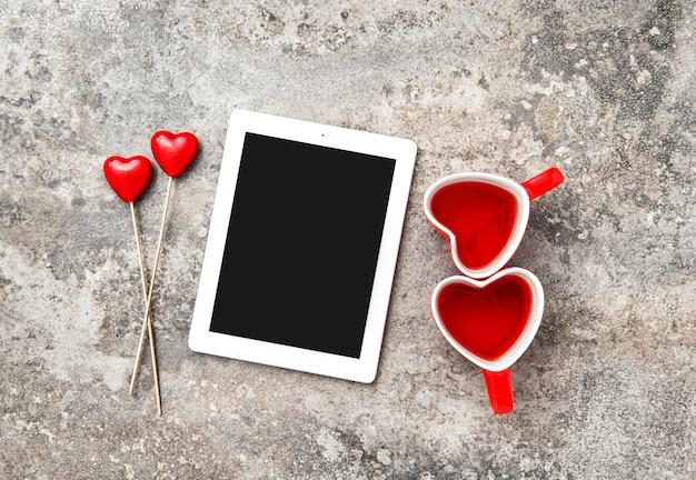 Copos de chá de coração vermelho tablet pc decorartion amor dia dos namorados Foto Premium