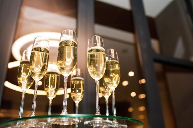 Copos de champanhe em uma mesa de vidro Foto Premium
