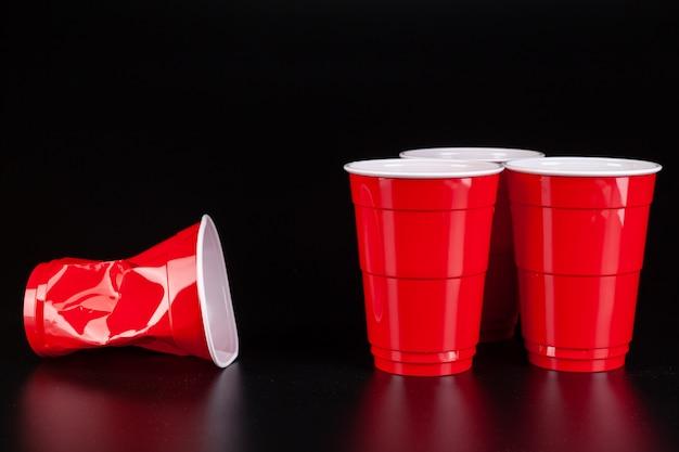 Copos de plástico vermelhos e bola para jogo de pong de cerveja Foto Premium