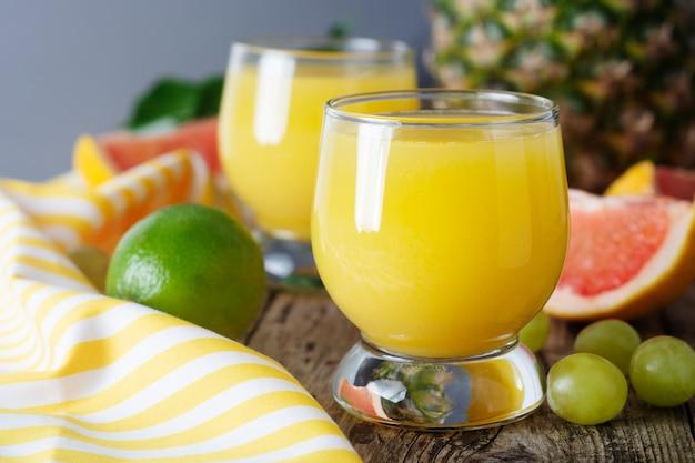 Copos de suco de frutas com frutas no fundo Foto Premium