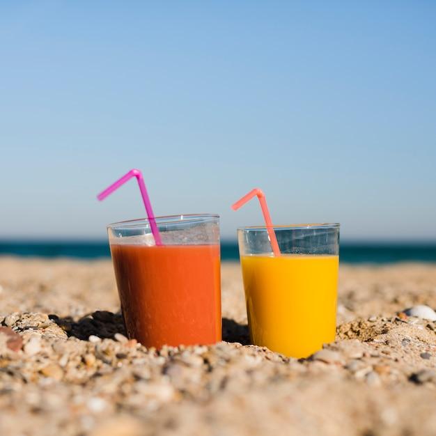 Copos de suco de laranja e amarelo com canudo na areia na praia contra o céu azul Foto gratuita