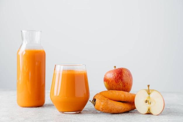 Copos de suco de laranja feito de cenoura e maçã, isolado no fundo branco Foto Premium