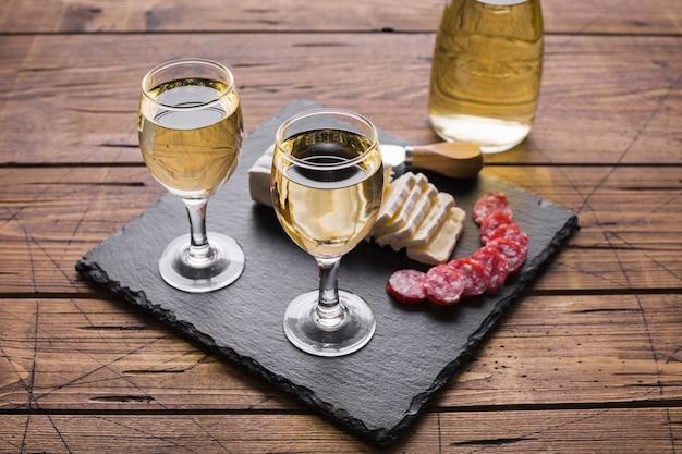 Copos de vinho branco de alta vista e queijo com salame Foto gratuita