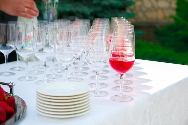 Copos de vinho, champanhe, pratos e frutas na toalha de mesa branca Foto Premium