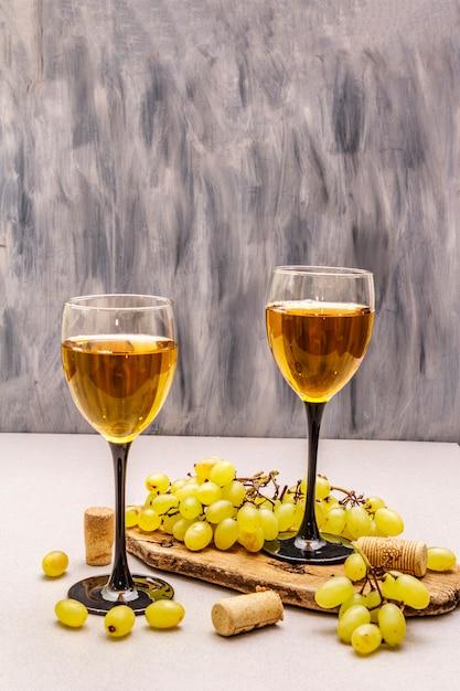 Copos de vinho, uvas frescas e rolhas na tábua de madeira Foto Premium